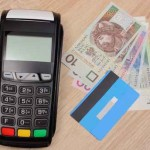 Payment terminal with credit card and polish money on desk, fina